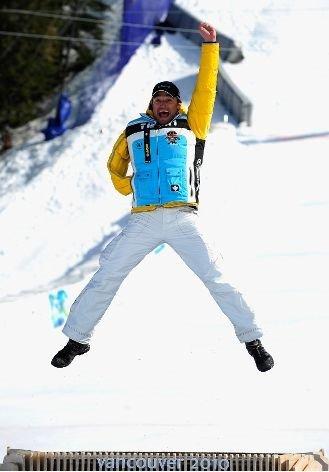 Fotografía de un esquiador amputado del brazo derecho saltando en el podio celebrando su medalla