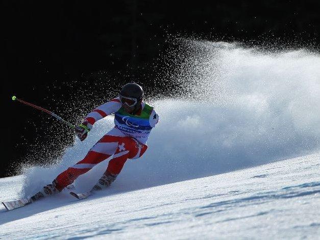 Fotografía de un esquiador de esquí de fondo amputado del brazo izquierdo en pista con una bonita estela de nieve detrás suyo
