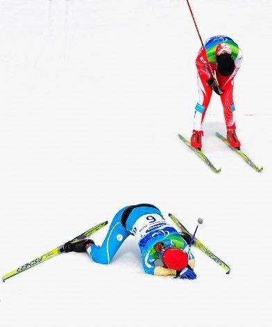 Fotografía de dos esquiadores de esquí de fondo en meta, unos de ellos en el suelo