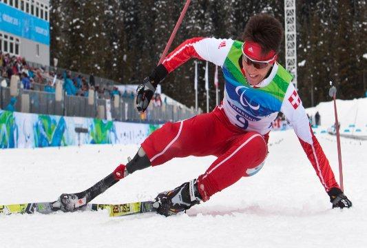 Fotografía de un esquiador de esquí alpino con prótesis debajo de la rodilla derecha levantandose del suelo
