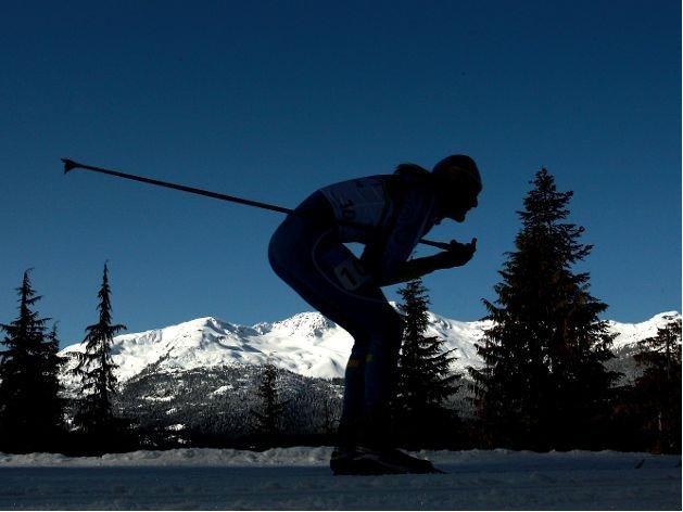 Fotografía de un participante de esquí de fondo en una pista, foto tomada en penumbra y con pinos y montañas al fondo
