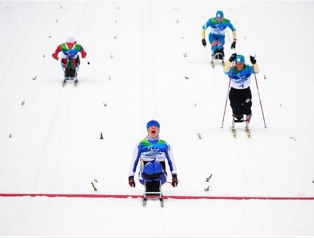Fotografía de varios participantes de esquí de fondo en silla cruzando la meta