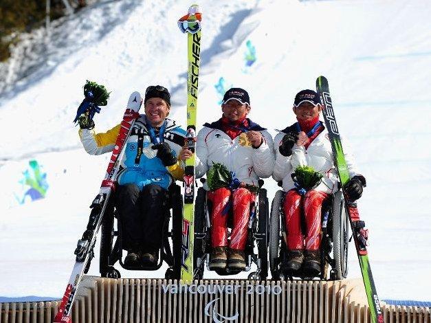 Fotografía de tres participantes de la categoria en silla en el podio