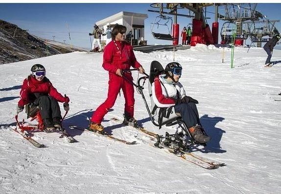 Fotografía de Profesor  acompañando a un alumno en silla de esquís