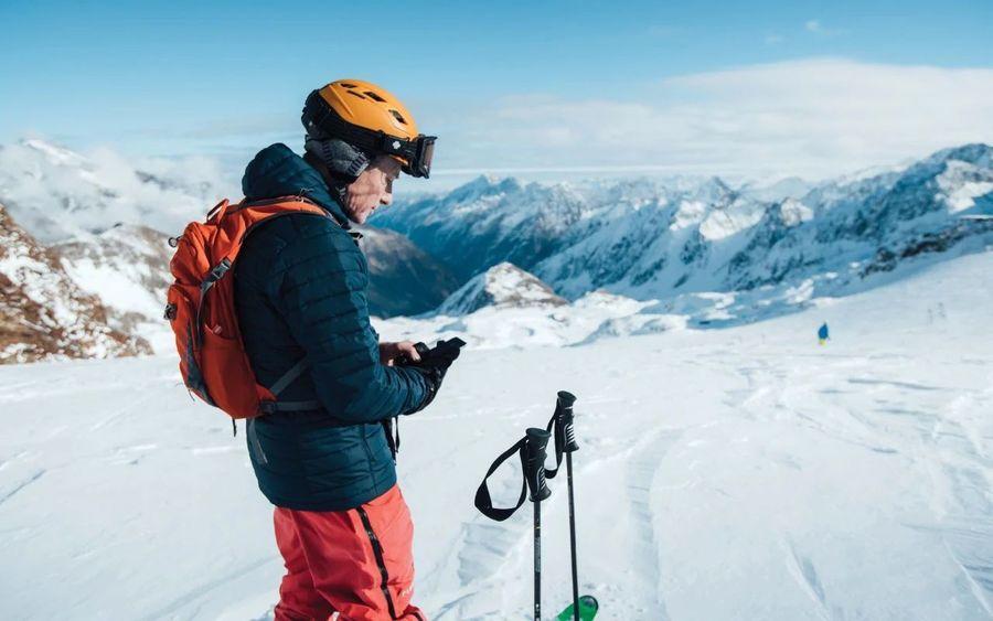 Esquiador con móvil en la mano mirando App