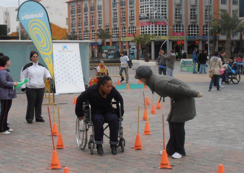 Fotografía de una chica probando una silla de ruedas.