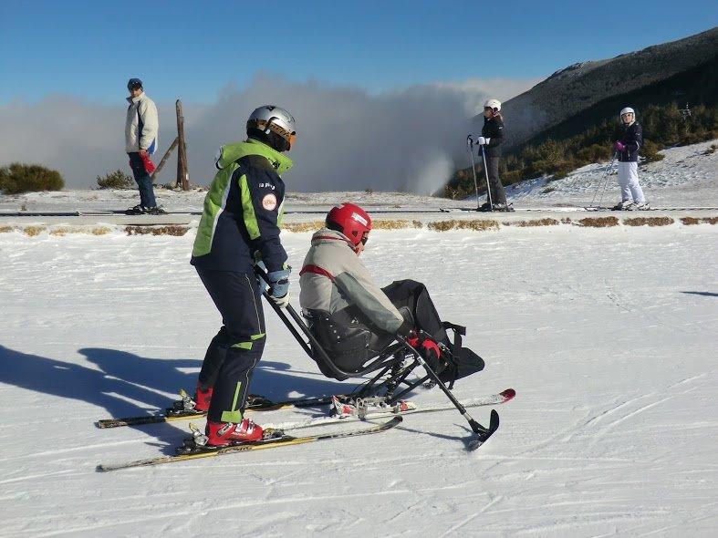 Fotografía de monitor de esquí bajandpo con discapacitado en silla