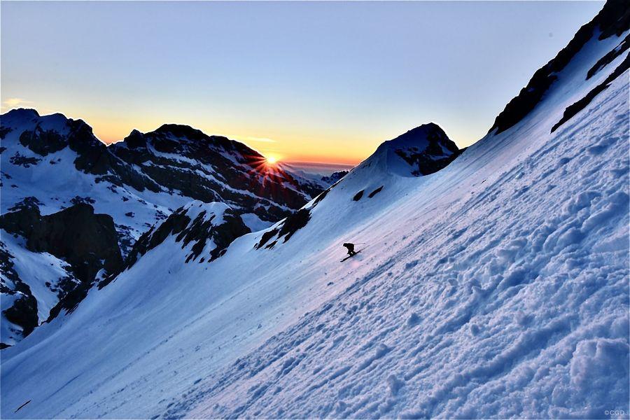 Pepín Román esquiando desde la cumbre del Tesorero con las últimas luces del dia iluminando las montañas mas altas de Cantabria, en el Macizo Central de los Picos de Europa.