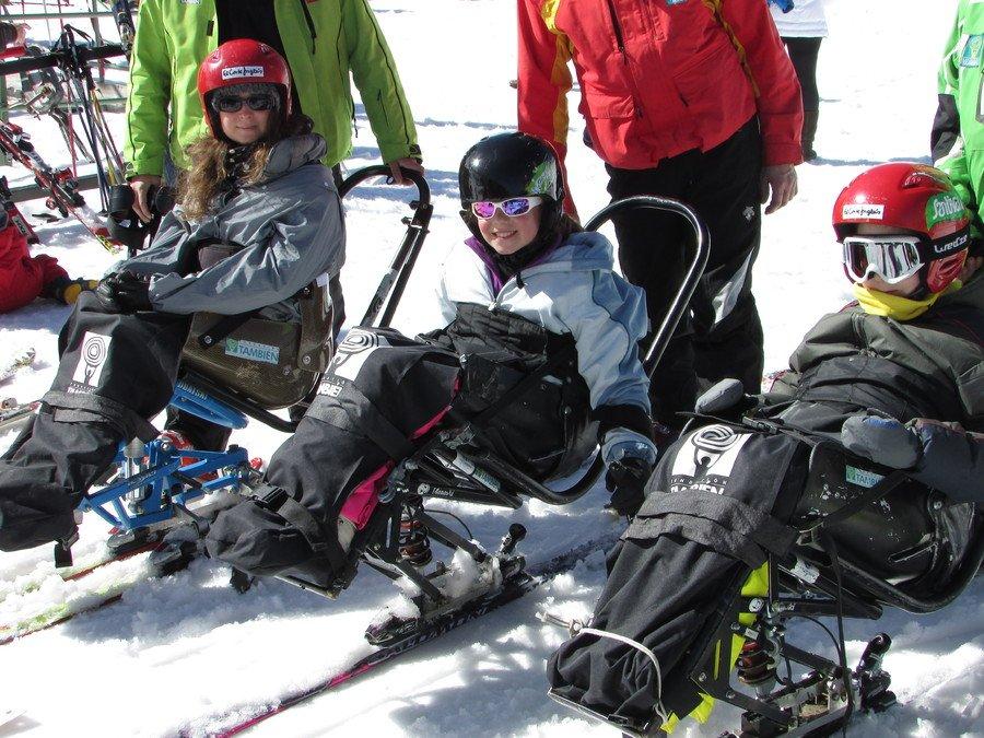Fotografía de tres niños en silla de esquí