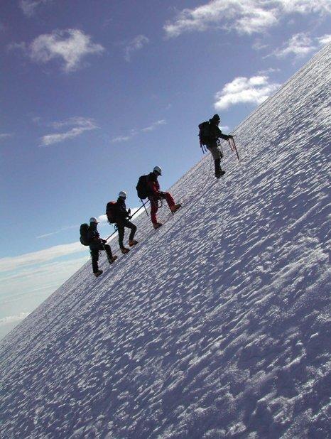 Fotografía de grupo ascendiendo por una montaña con hielo y nieve