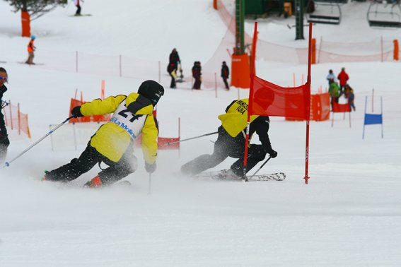 Fotografía de esquiador ciego con su guía, está sacada desde atrás
